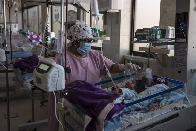 Una enfermera con mascarilla atiende a un bebé recién nacido en Bolivia.