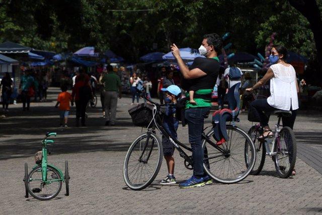Una familia pasea en bicicleta por el bosque de Chapultepec, un parque urbano si