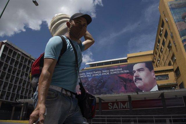Un hombre con mascarilla pasa ante un cartel con la imagen de Nicolás Maduro