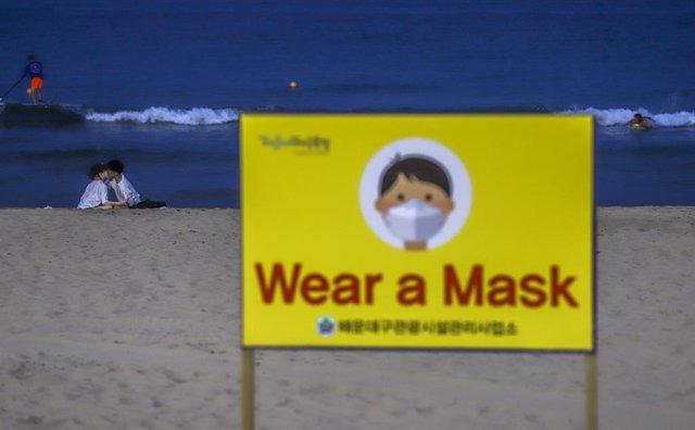 Un cartel animando al uso de la mascarilla en una playa de Corea del Sur