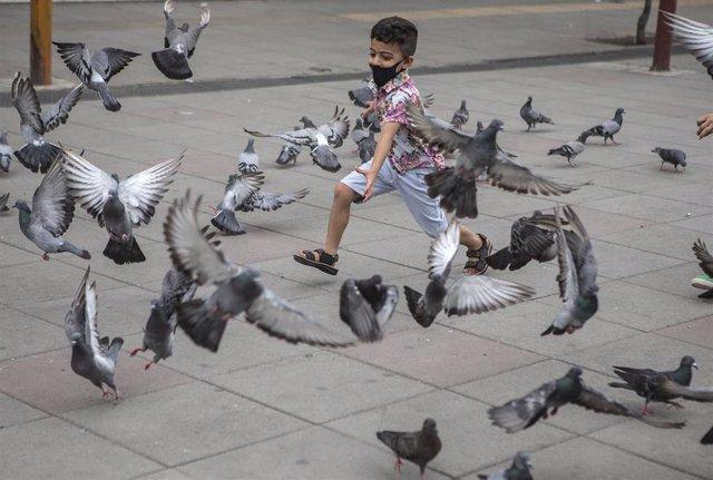 Un niño con mascarilla espanta a unas palomas en Teherán