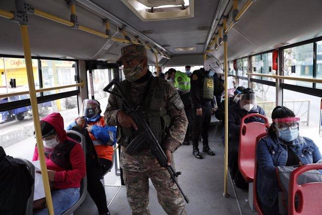 Un grupo de policías realizando labores de vigilancia y comprobando los permisos de circulación en un autobús de Lima, en medio de la crisis sanitaria provocada por la pandemia.