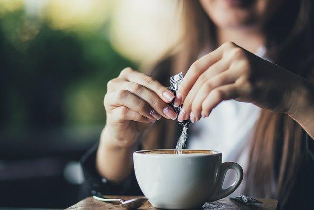 Mujer pone edulcorante en el café