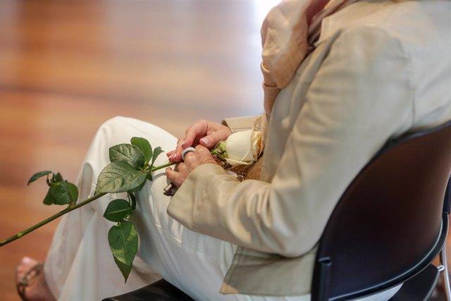 Detall d'una de les contrayentes subjectant una rosa blanca durant la celebració de les seves noces. A Madrid, (Espanya), a 13 de juny de 2020.