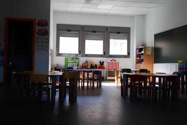 Sillas y mesas de un aula de un colegio, foto de archivo