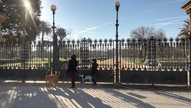 Dos mujeres pasean a sus perros por la entrada del Parc de la Ciutadella de Barcelona, cerrado