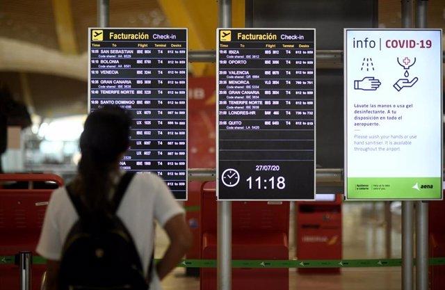 Un pasajero observa un panel de facturación en la terminal T1 del Aeropuerto Adolfo Suárez Madrid-Barajas