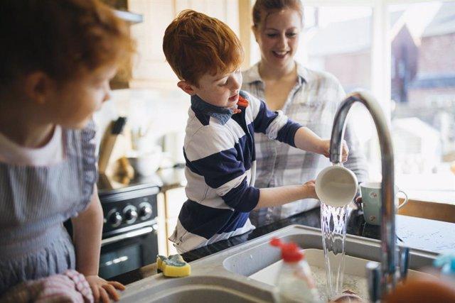 Niños fregando los platos con su madre en le cocina.