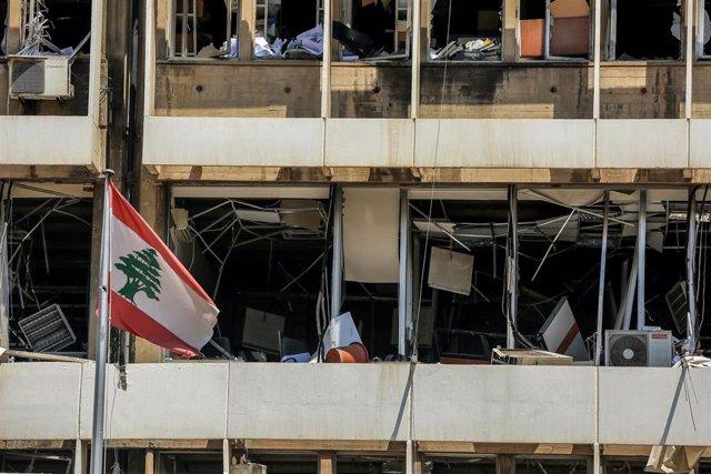 Una bandera de Líbano frente a un edificio dañado por las explosiones en el puerto de Beirut
