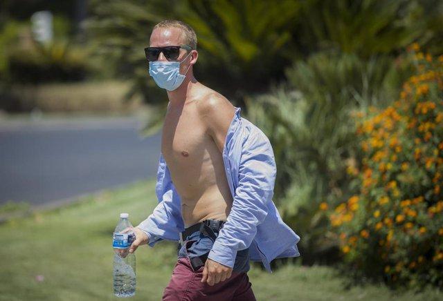 Un hombre con el torso descubierto y gafas de sol camina por la calle