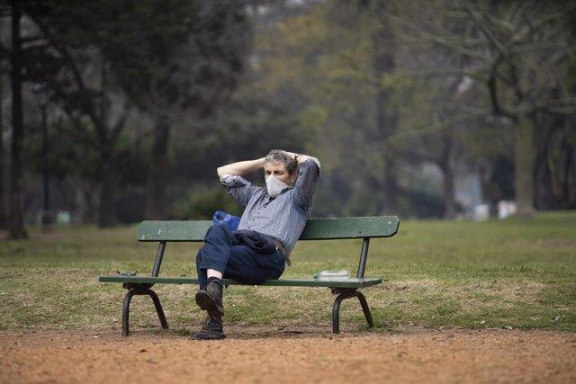 Un señor tomando la fresca en un parque de Buenos Aires, Argentina.