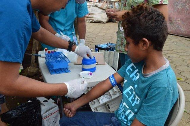 Un niño que participa en un estudio de cohorte longitudinal de enfermedades transmitidas por mosquitos en Managua, Nicaragua, presenta una muestra de sangre anual, como el zika o el dengue.