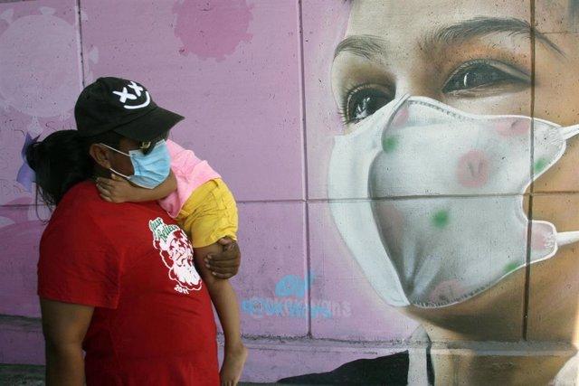 Una mujer camina por delante de un mural con mascarilla por el coronavirus en México.