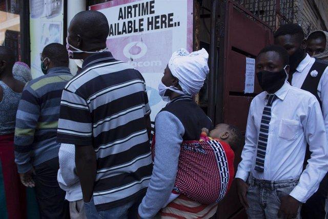 Personas con mascarilla en una cola para recibir alimentos durante la crisis del coronavirus en Pretoria, Sudáfrica