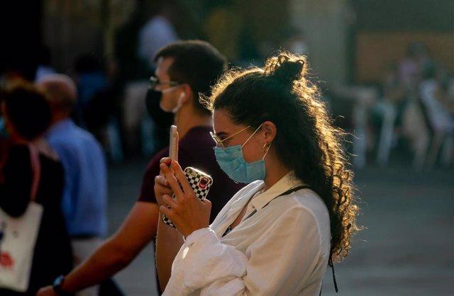 Una mujer consulta su smartfhone con una mascarilla puesta.