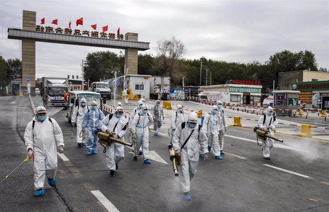 Trabajadores con trajes de protección desinfectan las calles en China por el coronavirus.