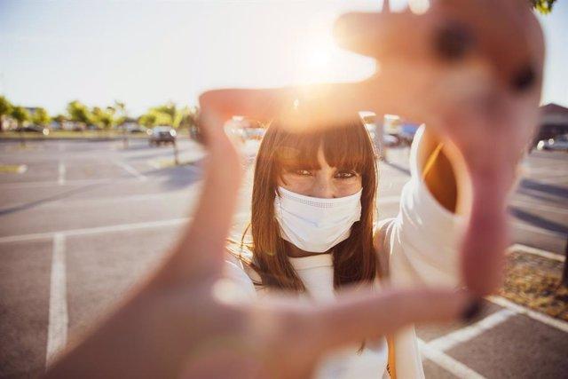 Mujer sonriendo con mascarilla higiénica.