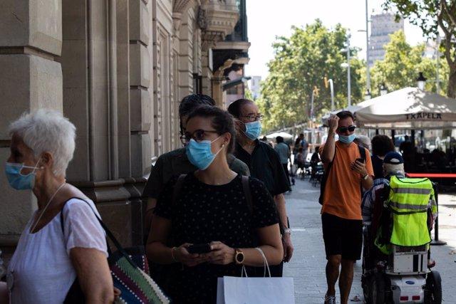 Desenes de persones protegides amb mascarilla fan cua per entrar en una biblioteca, a Barcelona, Catalunya (Espanya).