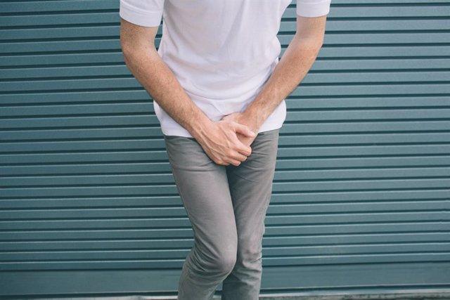 Hombre esperando en un urinario con ganas de entrar.