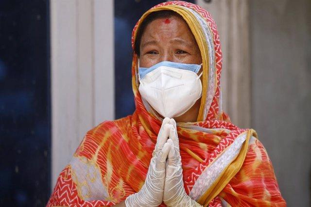 Una mujer con mascarilla llora por la muerte de un familiar por COVID-19 en Nepal