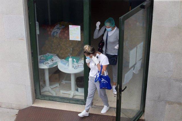 Dos mujeres a la entrada de la residencia de ancianos de O Incio, en Lugo (España), donde se ha detectado un brote de coronavirus, el 20 de agosto de 2020.