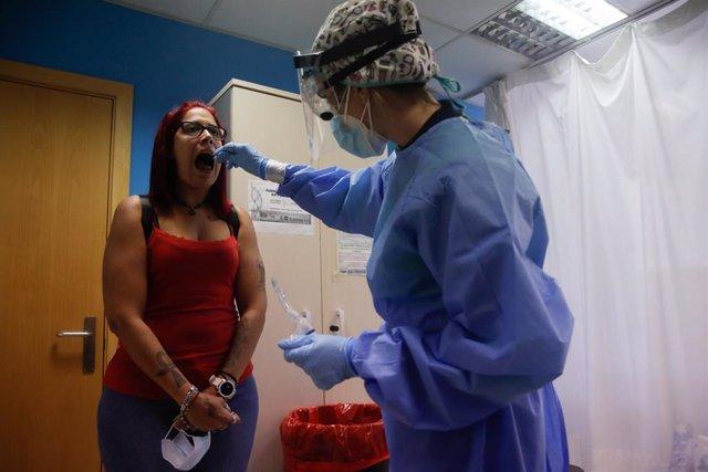 Una trabajadora sanitaria realiza una prueba PCR a una de las personas que ha acudido durante la jornada de hoy a realizarse un test al dispositivo instalado en el Centro de Especialidades El Arroyo, en Fuenlabrada, Madrid, (España), a 27 de agosto de 202