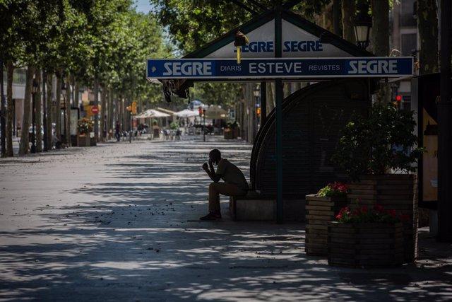 Un home descansa a l'ombra en un carrer de Lleida, capital de la comarca del Segrià, a Lleida, Catalunya (Espanya).