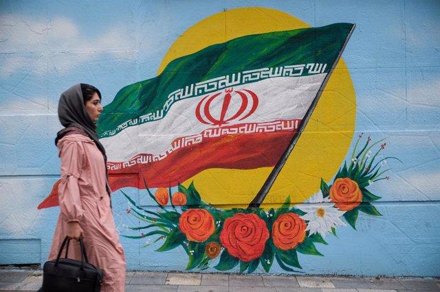Una mujer camina frente a un mural con la bandera de Irán situado en una de las