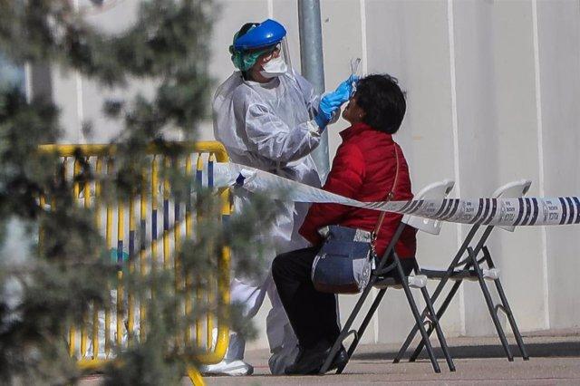 Una sanitaria realiza a una trabajadora de servicios esenciales uno de los test rápidos de coronavirus, foto de archivo