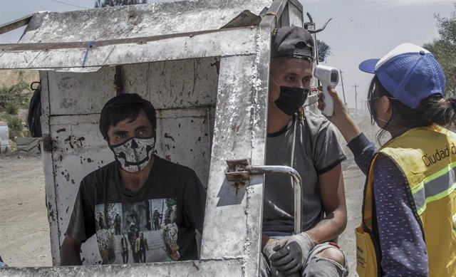 Toma de temperatura a dos trabajadores en un vertedero de México