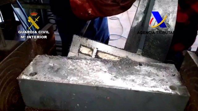 Agents de la Guàrdia Civil mostren un fragment de les encunyadores procedents de Colòmbia on estava amagada la droga.