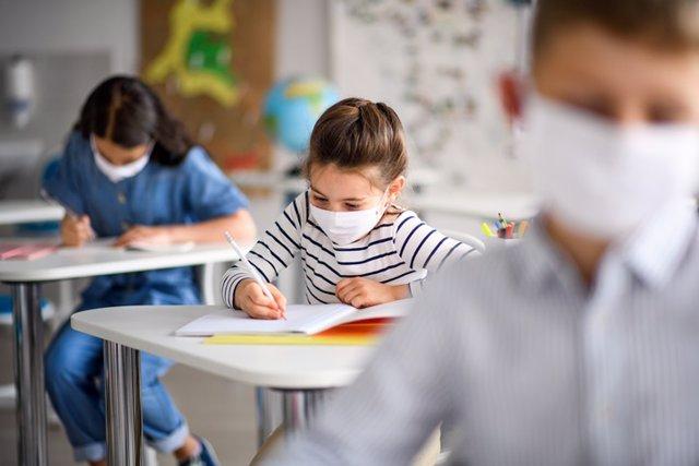 Niños en el colegio. Vuelta al cole. Niños mascarillas por coronavirus.
