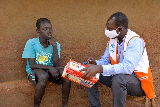 Un trabajador de World Vision entrega una radio a un niño en Uganda