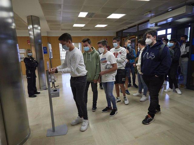 Alumnos de la UPNA se desinfectan las manos en un dispensador de gel hidroalcohólico a su entrada a las instalaciones de la Universidad el día en el que se celebra la apertura del curso 2020-2021, en Pamplona