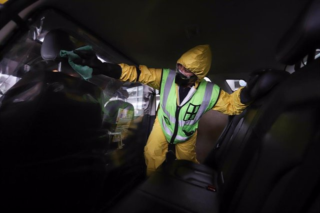 Una persona desinfecta un taxi a las puertas del Aeropuerto Internacional El Dorado, en Bogotá, Colombia.