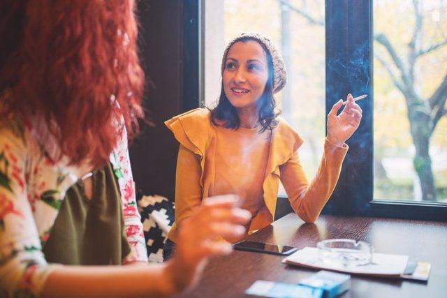 Mujeres fumando en un bar. Fumador social.