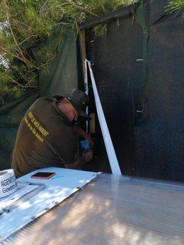 Un agente de Medio Ambiente precinta el chiringuito ilegal de Cala Varques (Manacor) con autorización judicial.