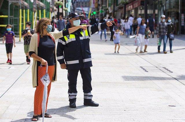 La cònsol major (alcaldessa) d'Andorra la Vella parla amb un agent de circulació en una de les vies més turístiques del país.
