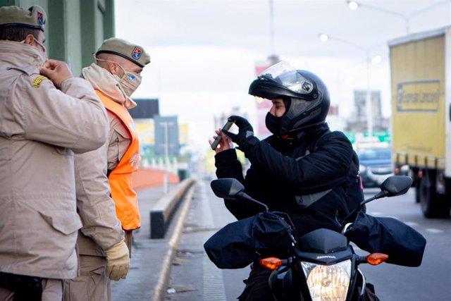 Un policía comprueba el permiso de un motorista en Buenas Aires