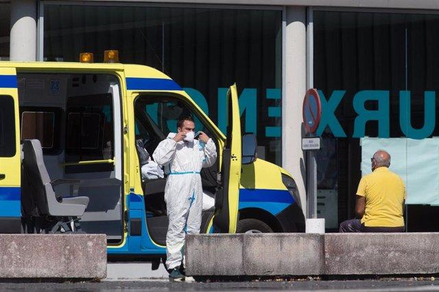 Un profesional sanitario baja de la ambulancia en la que viaja un paciente con Covid-19
