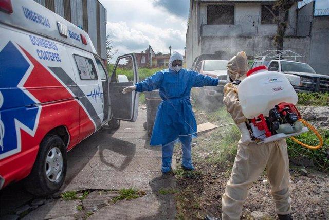 Un trabajador sanitario desinfecta su traje protector por el coronavirus.