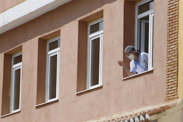 Una trabajadora se asoma a una ventana de  el centro de mayores Cáxar De La Vega, con un brote en la primera ola de la pandemia