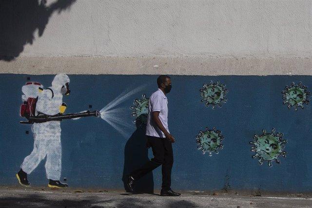 Un hombre con mascarilla camina delante de un mural sobre el coronavirus en Río de Janeiro