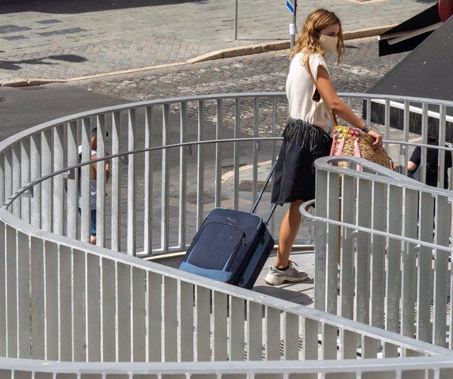 Una joven turista con maletas en el entorno de las Setas de la Encarnación, en  Sevilla a 3 de agosto del 2020