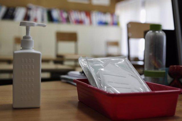 Mascarillas y gel desinfectante en la mesa del profesor de un aula donde se pueden observar los pupitres colocados y separados entre sí para el nuevo curso del colegio Virgen de Europa, debido a las nuevas medidas de distanciamiento que se han de tomar pa
