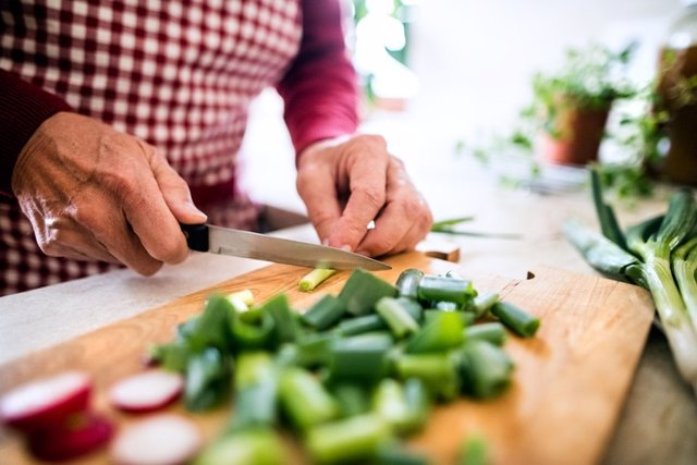 Hombre prepara comida en casa. Nutrición, dieta mediterranea.
