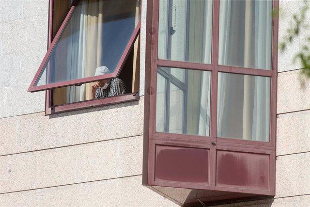 Una persona se asoma por la ventana de la residencia de mayores DomusVi de Outeiro de Rei en Lugo, Galicia (España).