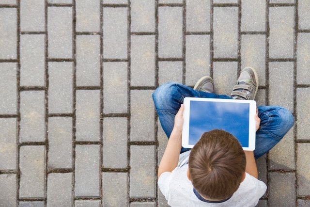 Child with tablet computer sitting outdoors. Education, learning, technology, friends