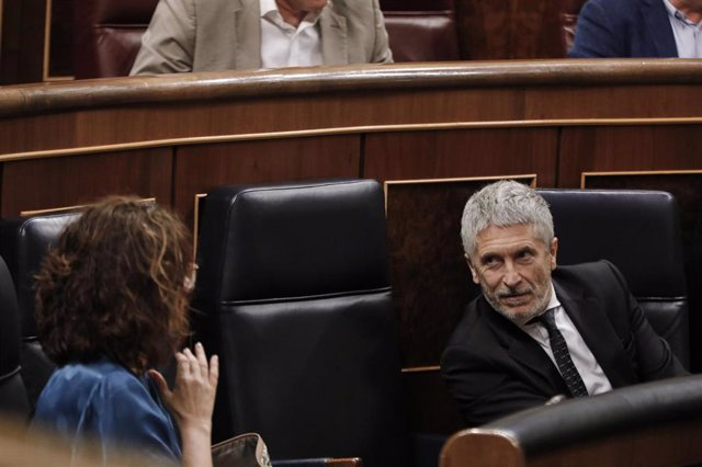 La ministra de Hacienda, María Jesús Montero, habla con el ministro del Interior, Fernando Grande-Marlaska, durante una sesión plenaria en el Pleno del Congreso en la que se votan las medidas de política social pactadas en el senado de la Comisión para la