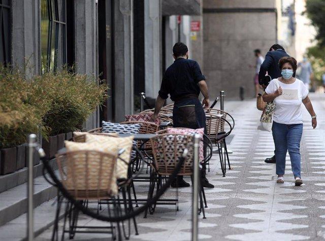 Un camarero prepara una terraza de un bar